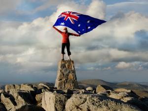 Man standing on Mt Kosciuszko with an Australian Flag
