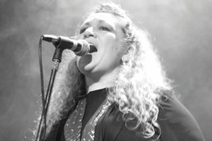 A Blues artist sings into a microphone on stage